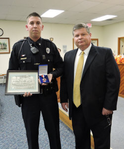 Aston Police Chief Dan Ruggieri (right) presented Officer Joshua Micun with a plaque of commendation for his heroic actions.