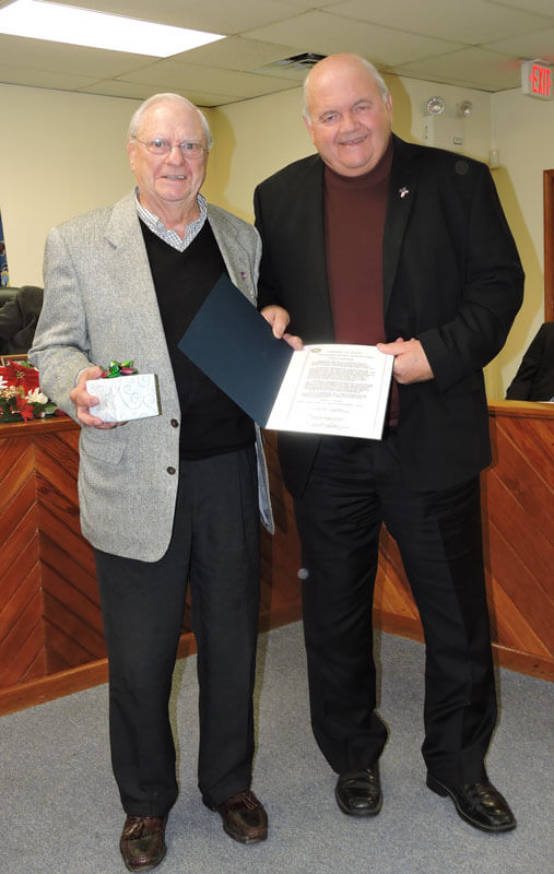 Aston Commissioner Jim McGinn, during the December 17 board of commissioners meeting, presented retired deputy health officer James Talbot with a proclamation and engraved wrist watch