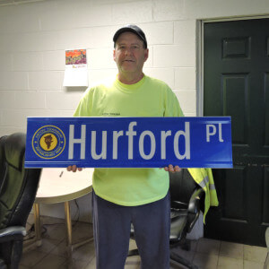 Aston Township Public Works Department Supervisor Russell Palmore displays one of the new street signs bearing the township logo.