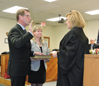 With his wife holding the Bible, new 1st Ward Commissioner Michael Link was sworn into office by Magisterial District Judge Diane Holefelder.  (photo by Loretta Rodgers)