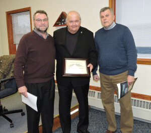 Aston 5th Ward Commissioner Jim McGinn, on behalf of the board of commissioners, accepts a certificate of appreciation from Aston Township Sports Hall of Fame committee members Kevin Talbot and Rob Locklear.